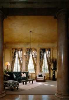 Vail Mansion museum style room with columns, tie dyed moire drapes lined in tea stained lace contemporary linen and leather chair, checkerboard ottoman