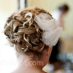 In lieu of a veil, two white silk organza flowers were pinned in the bride's curled updo. #wedding #hair #weddinghairstyles #updo