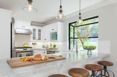 Eclectic Kitchen by Beth Dana Design via Houzz.  Painted cabs Benj Moore Simply White, Carrara countertops, Pottery Barn pendants, subway tile 8 X 2 1/2 is more modern that standard tile.