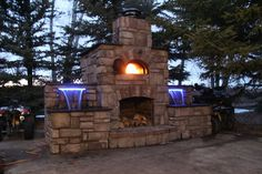 Outdoor brick and stone pizza (forno) oven. This pizza oven includes 2 waterfalls with LED lights.
