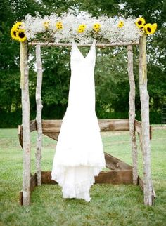 Wedding dress hanging on a sunflower backdrop @myweddingdotcom