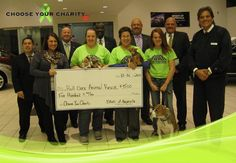 "Roll Over Animal Rescue reps, and their rescue pups, pose for their win in September's ""Choose your Charity"" contest."