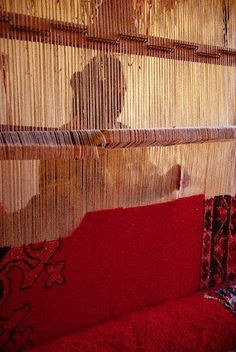 A Berber woman is silhouetted as she works at a loom with a partially woven carpet at an artisan ensemble in Ouarzazate, Morocco Style Marocain, Textiles, Berber Carpet, Magic Carpet, Travel And Tourism, North Africa, Handicraft, Rugs On Carpet, Fiber Art