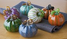 Mini Pumpkins by Leonoff Art Glass. As if freshly plucked from the vine, these petite blown glass pumpkins delight the eye with their rich colors, exquisite detail, and gracefully coiled stems. Each one is unique and will vary. Sold individually.In primary image, clockwise from bottom are: Steel Blue, Emerald Stripe, Berry, Turquoise, White Stripe, Halloween, and Russet with Green Stripe.In second image, clockwise from bottom left, colors are: Emerald Stripe, White Stripe, Russet with Green…