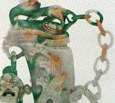 Here is a part of a jade vase that exemplifies a sculptural feat. It has been carved out of one solid piece of jade. We can see the chain to the right, attached in two places to the fine vase. This piece is an antique vase carved out of nephrite jade.