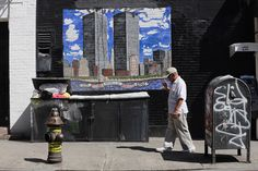A man walks past a mural depicting the twin towers on the 11th anniversary of the terrorist attacks on lower Manhattan at the World Trade Center on Sept. 11. (Mario Tama/Getty Images)