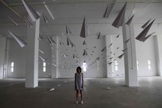 An art installation made with hundreds of paper airplanes by Dawn Ng.