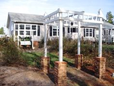 Brick, wood and pvc pipe pergola. Post set in concrete and brick mortared to post-pvc caps were drilled into 2x4's and with a great deal of patience and measuri…