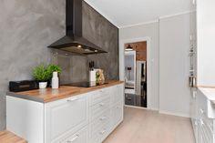 Kontrastvegg i kalkmaling bryter opp kjøkkenet på en fin måte.