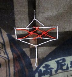 The small semamori (back talisman) in auspicious red and white silk thread depicts a child's top.