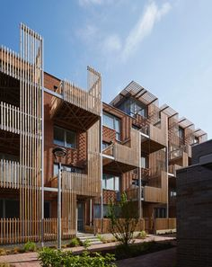 Vertical timber slats provide shade and privacy for staggered balconies arranged…