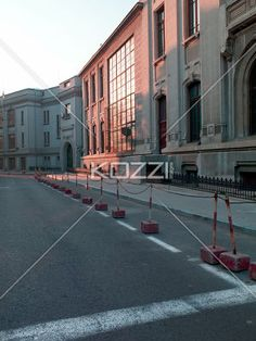 view of road barrier and building. - Image of road barrier on road with building in background.