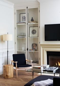 Enclosed french door built-in bookcases surround fireplace.