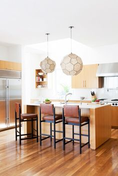 Chic leather bar stools and faceted pendant lighting in this Santa Monica kitchen
