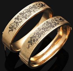 *A pair of Victorian gold and enamel bangles, circa 1870 The hinged bangles of textured rose gold design, the front and reverse decorated with varying black enamel panels of floral garland detail, the inside hoop of one bangle engraved 'Alina from Aunt Emma', mounted in gold.