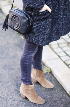 A grey coat is worn with blue corduroys, suede booties and a black crossbody bag.