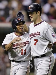 Minnesota Twins' Ben Revere (11) and Joe Mauer (7) celebrate Mauer's two-run home run off Cleveland Indians relief pitcher Tony Sipp in the seventh inning of a baseball game Saturday, June 2, 2012