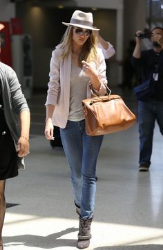 Rosie Huntington Whiteley wearing fedora hat, pastel pink blazer jacket, blue jeans, embroidered ankle boots and tan bag