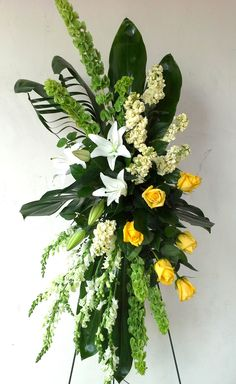 Sympathy Spray with white lilies, yellow roses, bells of ireland, white snapdragons and tropical foliage.