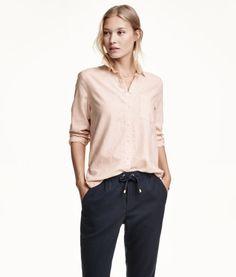 Gerade geschnittene Bluse aus weichem Baumwollflanell. Modell mit schmalem Turn-down-Kragen und einer Brusttasche. Rückenpasse mit Kellerfalte. Abgerundeter Saum mit etwas verlängertem Rückenteil.