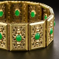 French 18K Gold and Green Stone Bracelet. A substantial and regal 1 inch wide bracelet comprised of twelve decoratively pierced and engraved plaques, crafted in rich 18 karat yellow gold centered with bright deep apple green cabochons that are not jade, but are dead ringers the real thing (we were fooled ((at first)) !). With French hallmarks