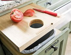 A pull-out cutting board has a hole, which makes it easy to brush the scraps straight into the trash bin just below.