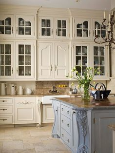 Cream kitchen cabinets, pale blue painted island. I would probably reverse it and do colored cabinets and cream island
