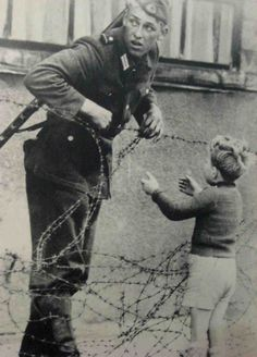 East German soldier helps a little boy over the wall who had been separated from his family at the beginning of construction. There is no record of how he was punished.