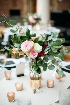 Silver dollar eucalyptus leaves coupled with a posy of saturated roses are an elegant addition to the formal dinner table.