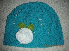 Gorro tejido a crochet con aplicación de rosa y hojas.