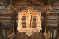 This wooden crucifix, which hangs suspended from the nave of St. David's Cathedral, is a fine 20th-century replacement for the destroyed medieval rood.    The four points of the cross contain the symbols of the four evangelists (eagle, ox, man, and lion), and two angels comfort Jesus from above (the one on the right is holding his hand).