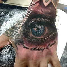 Realistic blue eye tattoo on hand by Emme Waddell tattoos & art.