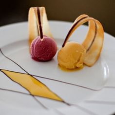Mango and Raspberry sorbets served with curved tuile cookies.