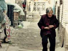 An Old Woman Walking Through The Streets Of Pingyao