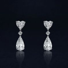 Crivelli. Pendant earrings made of white gold with heart cut diamonds and pear cut diamonds are the essence of light.