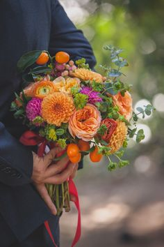 Pink, peach and coral bouquet with dahlias, garden roses, eucalyptus, hypericum berries, and ranunculus. The fresh kumquat fruits are a fun and unique touch!