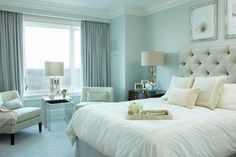 Gray and blue bedroom features walls painted blue lined with a gray tufted headboard on bed placed next to a curved wood nightstand and a gold metal circles lamp.