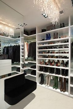 Awesome closet with a floating seat, large mirror, and pretty chandelier