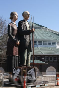"Experience Seward Johnson's ""God Bless America"" statue. Standing at 25 feet tall and weighing 5,900 pounds, the traveling sculpture depicts Grant Wood's ""American Gothic."" It will be on display every day in Pella Plaza."