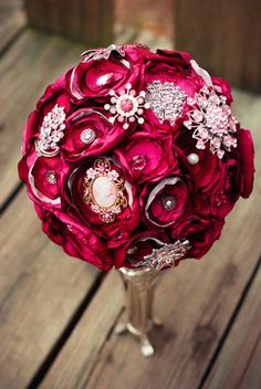 "Pink Brooch Wedding Bouquet by vinestjewelry. Mixes pink brooches and ""burned"" fabric flowers."