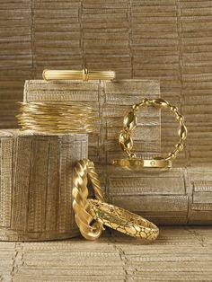 "Clockwise, from top: Medium-ridged Column bangle in 18k yellow gold from Slane & Slane. Faraone Mennella's Tuka-Tuka Big Ball bangle in 18k gold. Cartier's 18k Love bracelet. John Hardy's 18k Kali oval bangle. Crazy Twist bracelet in 18k yellow gold by Jean Schlumberger for Tiffany & Co. Ippolita's 18k Squiggle bangles. background: Maya Romanoff's ""Komodo"" Type II vinyl.   - Veranda.com"