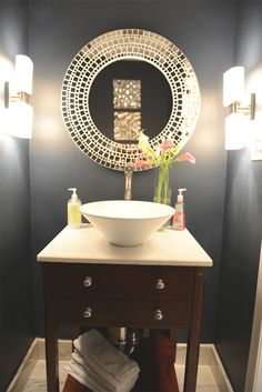 Simple bowl sink on top a table turned into a counter. Decorative mirror. Decorative light fixtures. Gray walls.