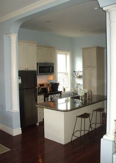 Small house kitchen. I like the island, window,and pseudo columns.