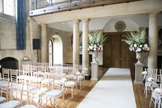 Ivory aisle carpet and tall stone plinth and urn arrangements with mixed roses and white #delphinium #weddingceremony http://www.collection26.com/weddings/blog/
