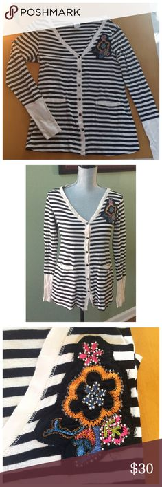 Anthro Stripe Cardigan with Floral Embellishment Black and white stripes, intact buttons, functional front pockets. Great condition! Some loose string pieces around embellishment, but I think that's part of the style. One sign of discoloration circled in last picture, but this is only on the inside collar. Brand is Tiny by Anthropologie. Anthropologie Sweaters Cardigans