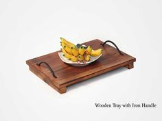 Wooden Tray with iron handle is stylish and versatile. It can be used to serve food or beverages and is made from lightly stained used wood.