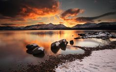 Coolio Blog: Snow covering mountains and rocks by a lake at sun...