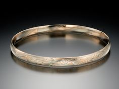 Mokume bangle bracelet in etched mokume of 14K palladium white gold, 14K red gold and sterling silver; 6mm wide.