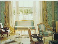 John Fowler's sitting room for Pauline de Rothchild. Pieced bicolor silk upholstered settee. White parquet floor, fur rugs, bow-ed curtains.