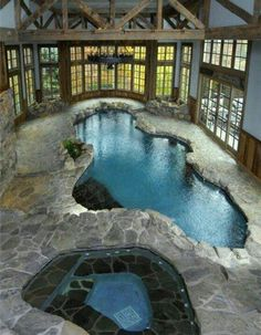 Rustic stone pool and hot tub with wood and windows